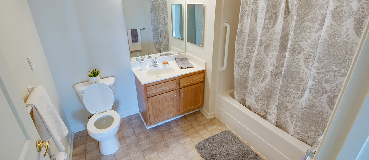 Bathroom with tile flooring and shower grab bars