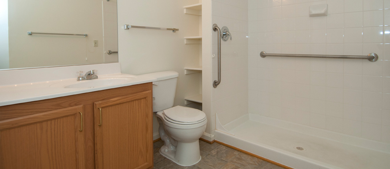 Bathroom with grab bars and storage shelves