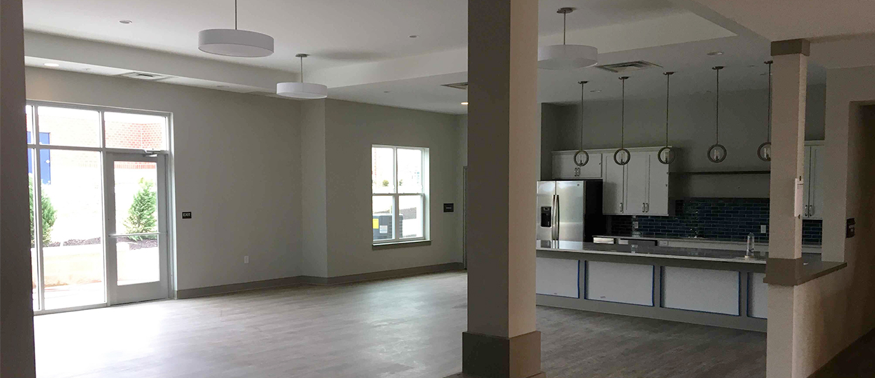 interior apartment with pillars and view of living room and kitchen